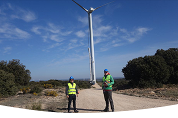 Two employees in front of the tower of a wind turbine